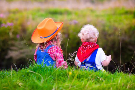 cowgirl hat: Little boy and girl dressed up as cowboy and cowgirl playing with toy rocking horse in park. Kids play outdoors. Children in Halloween costumes at trick or treat. Toys for preschooler or toddler child Stock Photo