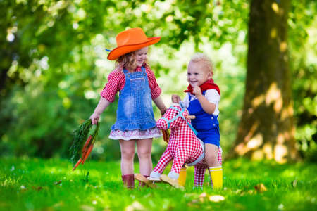cowboy boots: Little boy and girl dressed up as cowboy and cowgirl playing with toy rocking horse in park. Kids play outdoors. Children in Halloween costumes at trick or treat. Toys for preschooler or toddler child Stock Photo