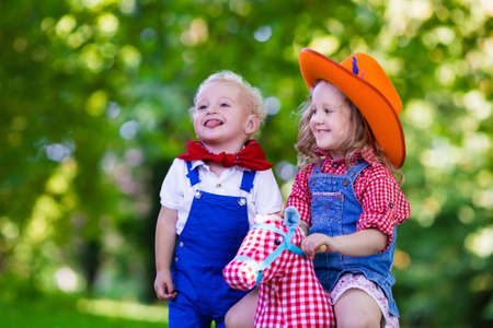 cowgirl and cowboy: Little boy and girl dressed up as cowboy and cowgirl playing with toy rocking horse in park. Kids play outdoors. Children in Halloween costumes at trick or treat. Toys for preschooler or toddler child Stock Photo