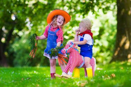 Weinig jongen en meisje verkleed als cowboy en cowgirl spelen met speelgoed hobbelpaard in het park. Kinderen spelen buiten. Kinderen in Halloween kostuums bij trick or treat. Speelgoed voor kleuter of peuter kind