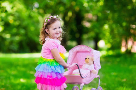 little girl dress: Little girl pushing toy stroller with bear. Toddler kid in pink dress playing with doll buggy. Kids birthday party. Children play outdoors. Mother and baby role game. Family summer fun. Preschool toys Stock Photo