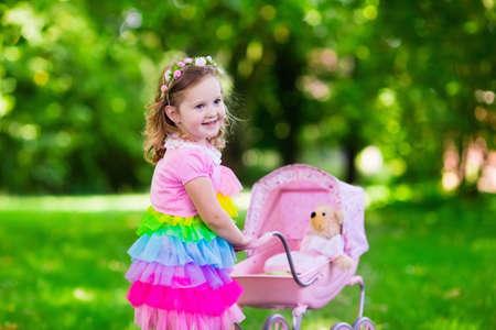 petite fille avec robe: Petite fille poussant jouet poussette avec ours. kid enfant en robe rose jouer avec la poup�e buggy. Enfants de f�te d'anniversaire. Les enfants jouent � l'ext�rieur. M�re et b�b� jeu de r�le. Famille plaisirs de l'�t�. Jouets pr�scolaires