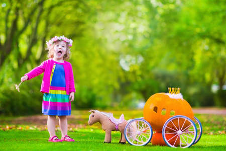 petite fille avec robe: Mignon boucl�s petite fille jouant Cendrillon conte de f�e tenant baguette magique � c�t� d'un chariot de citrouille dans le parc de l'automne � l'Halloween. Trick or treat enfants au champ de citrouilles. Famille avec enfants de d�couper.