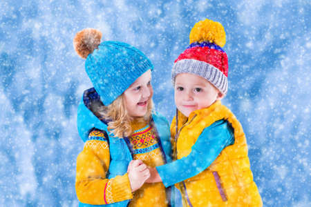two hands: Little girl and boy in yellow and blue knitted hat catching snowflakes in winter park on Christmas eve. Kids play outdoor in snowy winter forest. Children catch snow flake on Xmas. Toddler kid playing