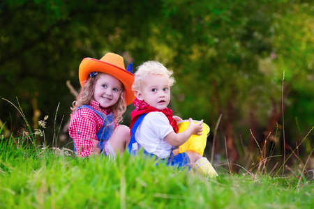 cowgirl boots: Little boy and girl dressed up as cowboy and cowgirl playing with toy rocking horse in park. Kids play outdoors. Children in Halloween costumes at trick or treat. Toys for preschooler or toddler child Stock Photo