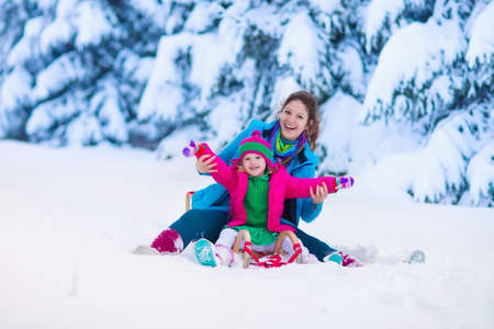 screaming: Young mother and little girl enjoying sleigh ride. Child sledding. Toddler kid riding sledge. Children play outdoors in snow. Kids sled in snowy park. Outdoor winter fun for family Christmas vacation.