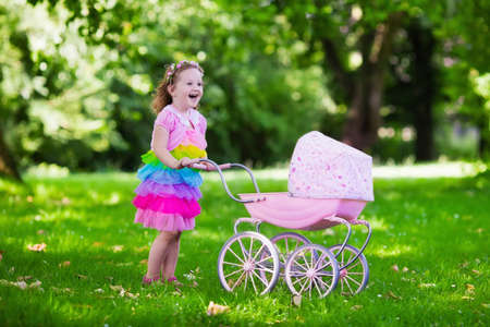 family with baby: Little girl pushing toy stroller with bear. Toddler kid in pink dress playing with doll buggy. Kids birthday party. Children play outdoors. Mother and baby role game. Family summer fun. Preschool toys Stock Photo