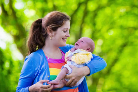 mom kiss son: Mother holding newborn baby in a park. Mom playing with her new born son in the garden. Family with kids play outdoors. Young woman hugging little boy. Parents and children having fun in summer.