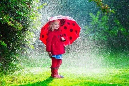 botas de lluvia: Niña con el paraguas rojo que juega en la lluvia. Los niños juegan al aire libre por el tiempo lluvioso en el otoño. Otoño diversión al aire libre para los niños. Chico Niño en impermeable y botas para caminar en el jardín. Ducha de verano.