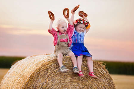 oktoberfest: Kids in traditional Bavarian costumes in wheat field. German children eating bread and pretzel during Oktoberfest in Munich. Brother and sister play at hay bales during autumn harvest time in Germany
