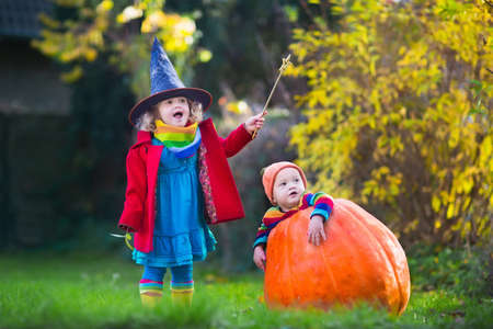 Little girl in witch costume and baby boy in huge pumpkin playing in autumn park. Kids at Halloween trick or treat. Toddler with jack-o-lantern. Children with candy bucket in forest. Banque d'images
