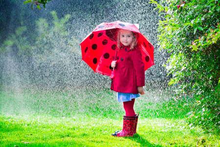 빨간 우산 빗 속에서 재생 어린 소녀. 아이들은 가을에 비가 오는 날씨에 야외에서 재생할 수 있습니다. 어린이를위한 가을 야외 재미. 유아 비옷에 아