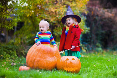 witch spider: Little girl in witch costume and baby boy in huge pumpkin playing in autumn park. Kids at Halloween trick or treat. Toddler with jack-o-lantern. Children with candy bucket in forest. Stock Photo