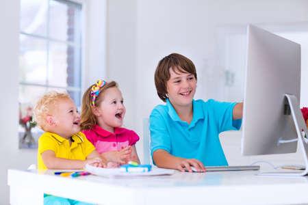 집에서 개인 컴퓨터에서 작동하는 학교 아이. 학생 교실에서 현대적인 PC를 사용하여 숙제. 디지털 기기와 함께 공부하는 아이입니다. 아이들은 흰색  스톡 콘텐츠