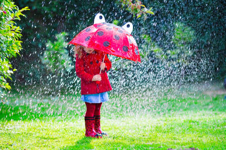 rain boots: Ni�a con el paraguas rojo que juega en la lluvia. Los ni�os juegan al aire libre por el tiempo lluvioso en el oto�o. Oto�o diversi�n al aire libre para los ni�os. Chico Ni�o en impermeable y botas para caminar en el jard�n. Ducha de verano.
