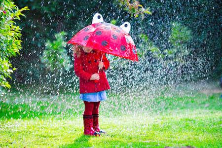 mignonne petite fille: Petite fille avec parapluie rouge jouant sous la pluie. Les enfants jouent à l'extérieur par temps de pluie à l'automne. Automne plaisir en plein air pour les enfants. enfant en bas âge en imperméable et des bottes de marche dans le jardin. douche d'été.