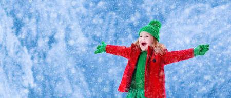 Dziewczynka w czerwonej kurtce i zielona czapka łowienie śniegu w zimie park w Wigilię. Dzieci grać na świeżym powietrzu w snowy leśnej. Dzieci złapać płatki śniegu na Boże Narodzenie. Maluch dzieciak gra.