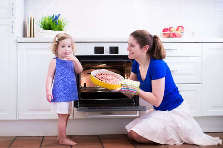 white kitchen: Mother and child bake a pie. Young woman and her daughter cook in a white kitchen. Kids baking pastry. Children helping to make dinner. Modern interior with oven and other appliances. Family eating.