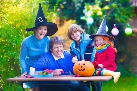 frutas divertidas: Familia tallar calabazas en Halloween. Vestida truco niño o el tratamiento. Los niños y los padres trick or treat. Niño en el traje de bruja de juego en el parque de otoño. Chico Niño con jack-o-lantern.
