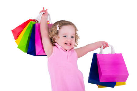 niños de compras: Little girl  in a pink dress holding colorful shopping bags. Child in a shop buying clothes. Sale in a store. Kids with purchases.