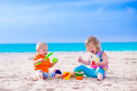 preschooler: Kids play on a beach. Children building sand castle on tropical island. Summer water fun for family. Boy and girl with toy buckets and spade at the sea shore. Ocean vacation with baby and toddler kid.
