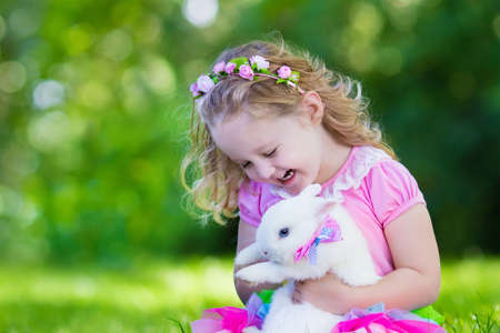 child laughing: Children play with real rabbit. Laughing child at Easter egg hunt with white pet bunny. Little toddler girl playing with animal in the garden. Summer outdoor fun for kids with pets. Stock Photo