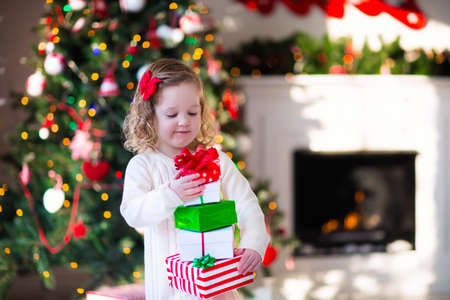 white christmas tree: Family on Christmas morning at fireplace. Kids opening Xmas presents. Children under Christmas tree with gift boxes. Decorated living room with traditional fire place. Cozy warm winter day at home. Stock Photo