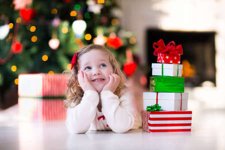 new: Family on Christmas morning at fireplace. Kids opening Xmas presents. Children under Christmas tree with gift boxes. Decorated living room with traditional fire place. Cozy warm winter day at home. Stock Photo