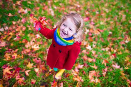 enfant qui joue: Petite fille avec des feuilles jaunes. Enfant jouant avec les feuilles d'automne d'or. Les enfants jouent en plein air dans le parc. Enfants de randonnée dans la forêt d'automne. kid enfant sous un arbre d'érable sur une journée ensoleillée Octobre.