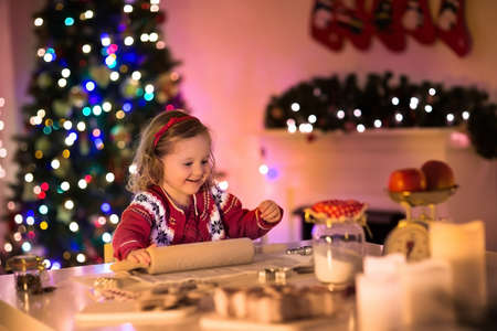 dining room: Little girl baking Christmas pastry. Children bake gingerbread. Toddler child preparing cookie for family dinner on Xmas eve. Decorated kitchen or dining room with fireplace, tree, candles and lights Stock Photo