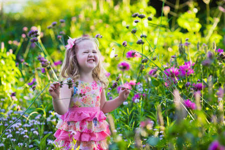 garden flowers: Little girl playing with flowers in the garden. Kids play outdoors in summer. Children gardening. Child planting flower in the backyard. Gardener at work. Kid working with plants.