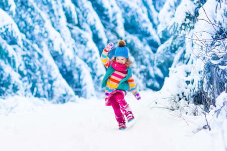 Little girl enjoying a sleigh ride. Child sledding. Toddler kid riding a sledge. Children play outdoors in snow. Kids sled in the Alps mountains in winter. Outdoor fun for family Christmas vacation. Foto de archivo