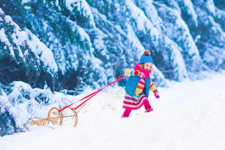 kinderschoenen: Meisje genieten van een sledetocht. Kind sleeën. Peuter jongen rijden op een slee. De kinderen spelen buiten in de sneeuw. Kinderen slee in de bergen Alpen in de winter. Outdoor plezier voor familie kerstvakantie.