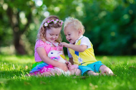 children at play: Children play with real rabbit. Brother and sister at Easter egg hunt with white pet bunny. Little baby boy and toddler girl playing with animal in the garden. Summer outdoor fun for kids with pets. Stock Photo