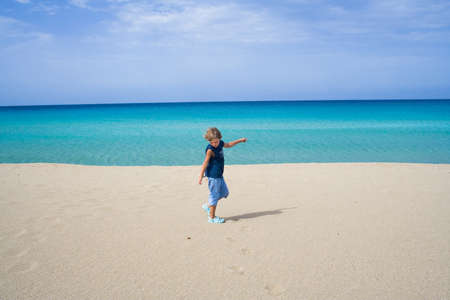 blue sea: Little boy playing and dancing in the ocean on a tropical beach