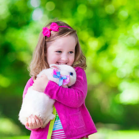 for kids: Children play with real rabbit. Laughing child at Easter egg hunt with white pet bunny. Little toddler girl playing with animal in the garden. Summer outdoor fun for kids with pets. Stock Photo