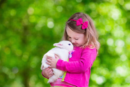Children play with real rabbit. Laughing child at Easter egg hunt with white pet bunny. Little toddler girl playing with animal in the garden. Summer outdoor fun for kids with pets. Stock Photo