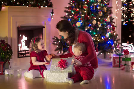 baby open present: Family on Christmas eve at fireplace. Mother and little kids opening Xmas presents. Children with gift boxes. Living room with traditional fire place and decorated tree. Cozy winter evening at home.