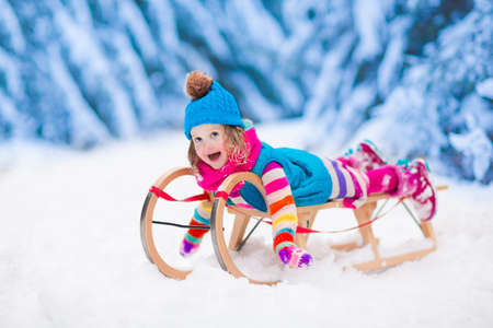Little girl enjoying a sleigh ride. Child sledding. Toddler kid riding a sledge. Children play outdoors in snow. Kids sled in the Alps mountains in winter. Outdoor fun for family Christmas vacation. Standard-Bild