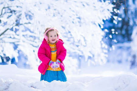 children at play: Little girl enjoying a sleigh ride. Child sledding. Toddler kid riding a sledge. Children play outdoors in snow. Kids sled in the Alps mountains in winter. Outdoor fun for family Christmas vacation. Stock Photo