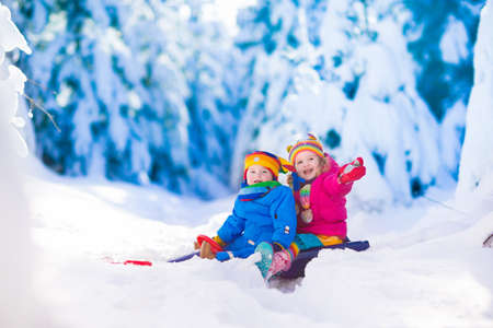 Little girl and baby boy enjoying a sleigh ride. Child sledding. Toddler kid riding a sledge. Children play outdoors in snow. Kids sled in snowy park. Outdoor winter fun for family Christmas vacation.