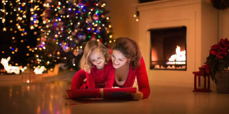 Mother and daughter read a book at fireplace on Christmas eve. Family with child celebrating Xmas. Decorated living room with tree, fire place and candles. Winter evening at home for parents and kids. Stock Photo