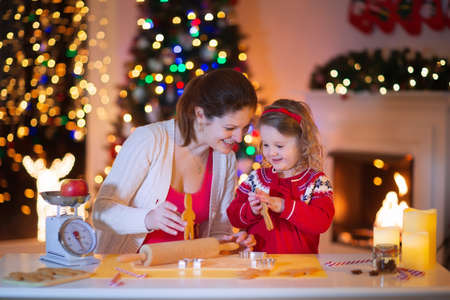 galletas: Madre y niña hornear pasteles de Navidad. Niños hornear pan de jengibre. Infante Niño preparar galletas para la cena familiar en la víspera de Navidad. Cocina decorada o comedor con chimenea, árbol, velas.