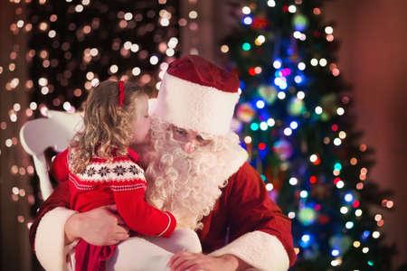 Santa Claus y los niños que abren presentes en la chimenea. Los niños y el padre en el traje de Santa y barba abierta regalos de Navidad. Niña que ayuda con el actual saco. Familia bajo el árbol de Navidad en la chimenea. Foto de archivo