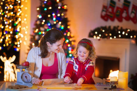 holiday home: Mother and little girl baking Christmas pastry. Children bake gingerbread. Toddler child preparing cookie for family dinner on Xmas eve. Decorated kitchen or dining room with fireplace, tree, candles. Stock Photo
