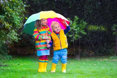 botas de lluvia: Niña y niño con el paraguas de colores que juegan en la lluvia. Los niños juegan al aire libre en tiempo de lluvia en otoño. Diversión del otoño para los niños. Chico Niño en impermeable y botas a pie en el jardín. Ducha de verano Foto de archivo