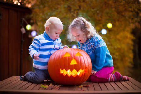trick or treat: Little girl and boy carving pumpkin at Halloween. Dressed up children trick or treating. Kids trick or treat. Child in witch costume playing in autumn park. Toddler kid with jack-o-lantern.