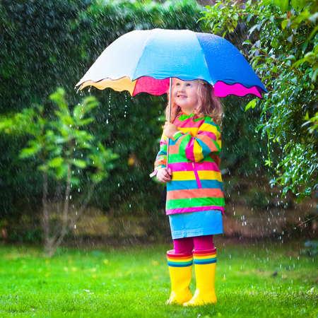 雨の中で遊ぶカラフルな傘と女の子。子供秋の雨の天候で外で遊ぶ。子どもたちに秋の楽しい。幼児子供レインコートと園内を歩くブーツ。夏のシ