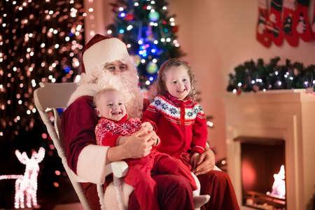 under fire: Santa Claus y los niños que abren presentes en la chimenea. Los niños y el padre en el traje de Santa y barba abierta regalos de Navidad. Niña que ayuda con el actual saco. Familia bajo el árbol de Navidad en la chimenea. Foto de archivo