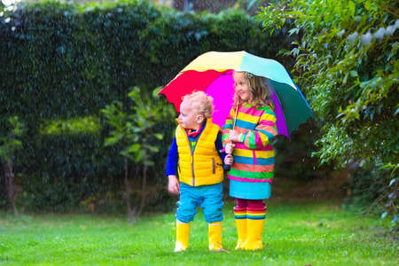 kids outside: Little girl and boy with colorful umbrella playing in the rain. Kids play outdoor by rainy weather in fall. Autumn fun for children. Toddler kid in raincoat and boots walk in the garden. Summer shower